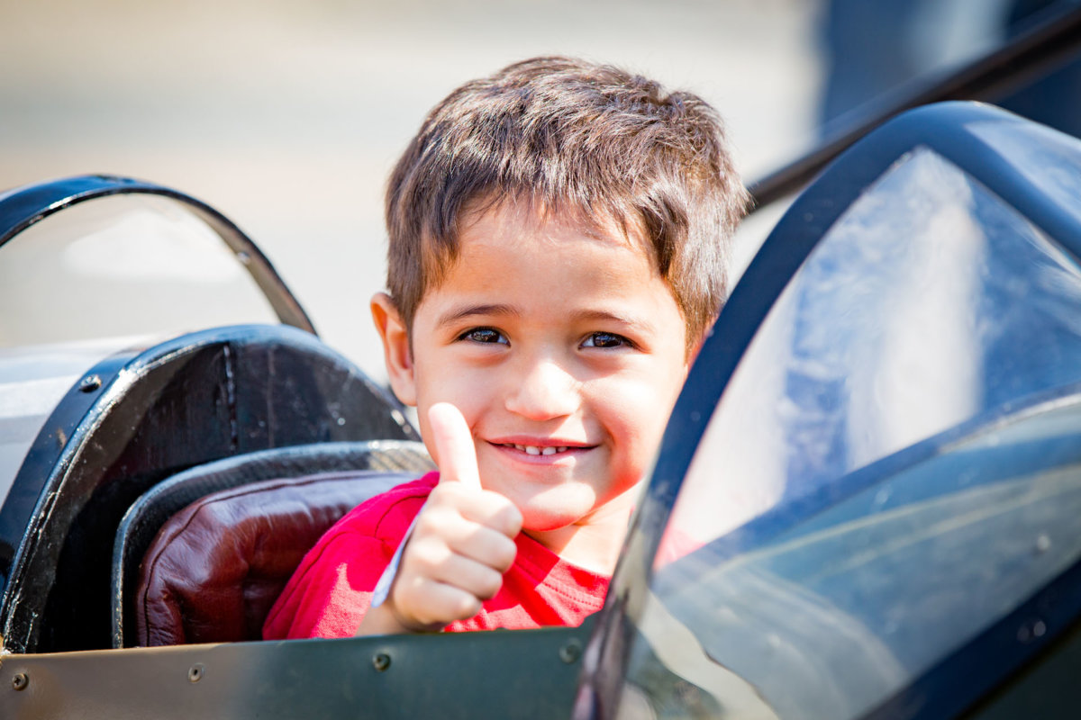 Child putting his thumbs up while in a plane
