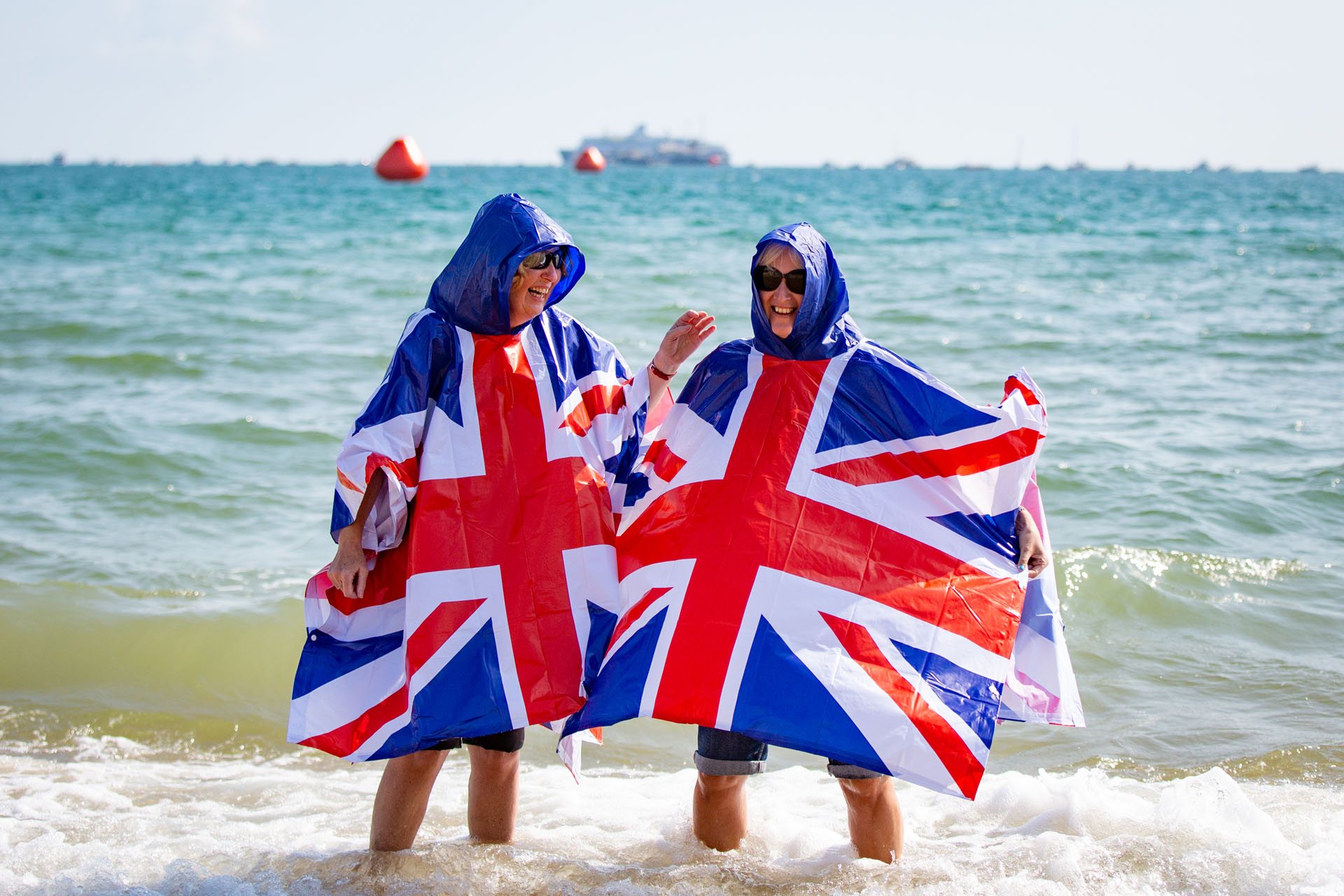 Two woman standing in the seat showing off their Union jack ponchos