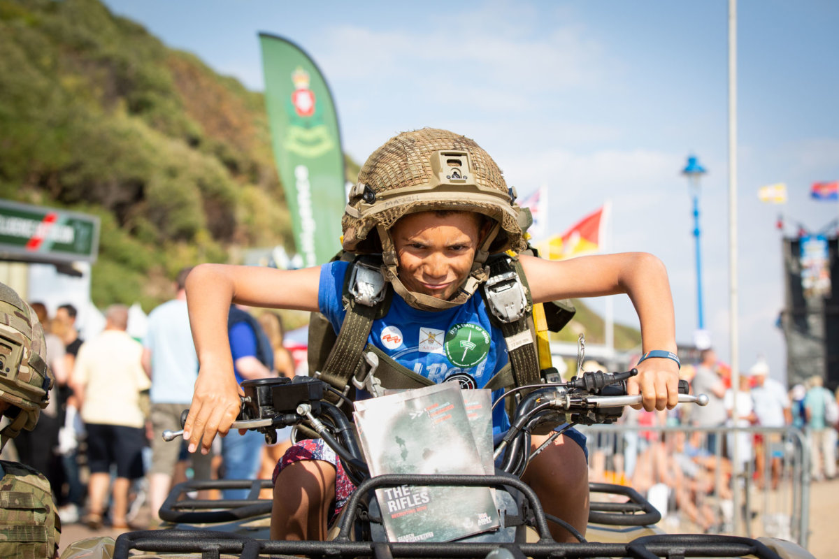 Child dressed up in army gear whilst sat on a quad bike