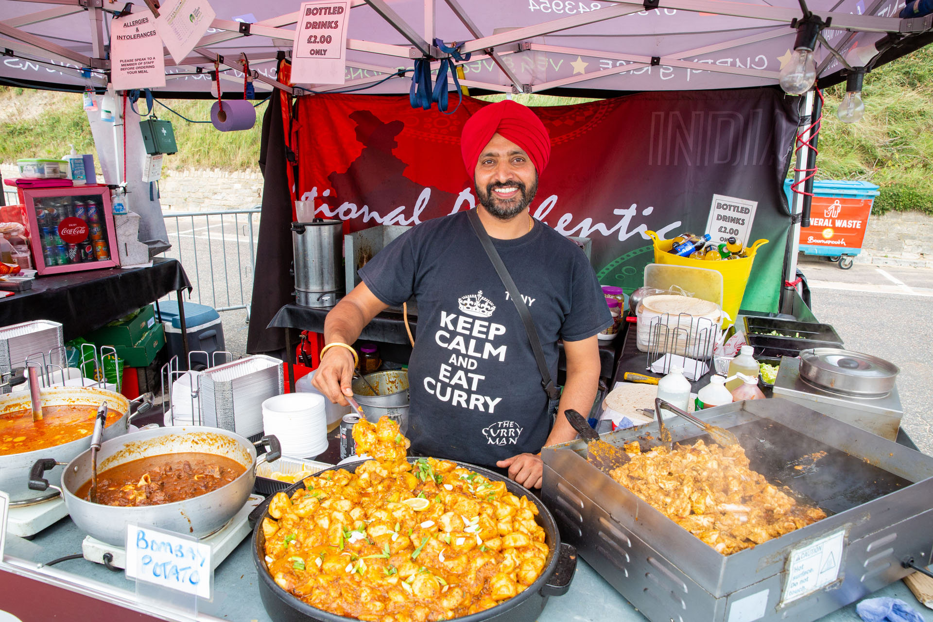 Vendor show casing his delicious and fresh array of Indian dishes to the camera