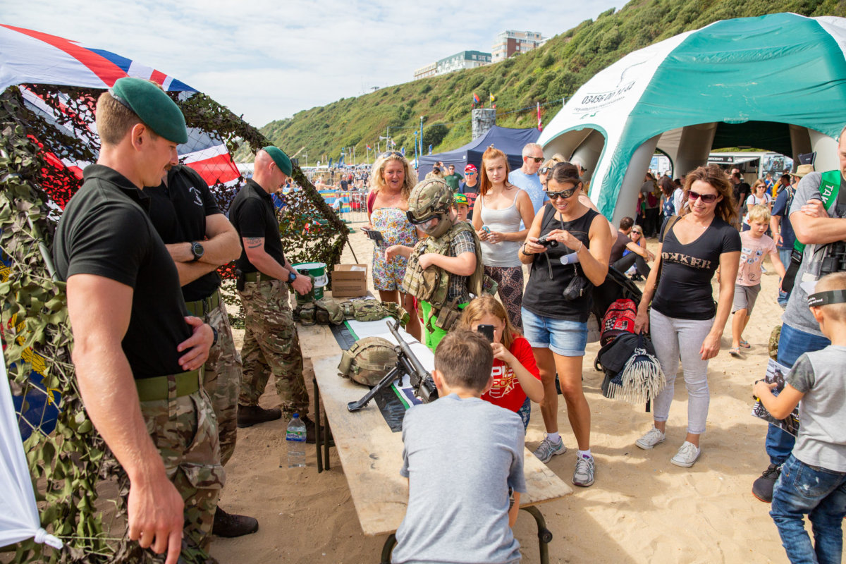 Kids and adults interacting with the army exhibition