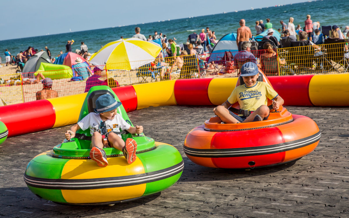 Two kids enjoying the blow up bumper cars on the beach