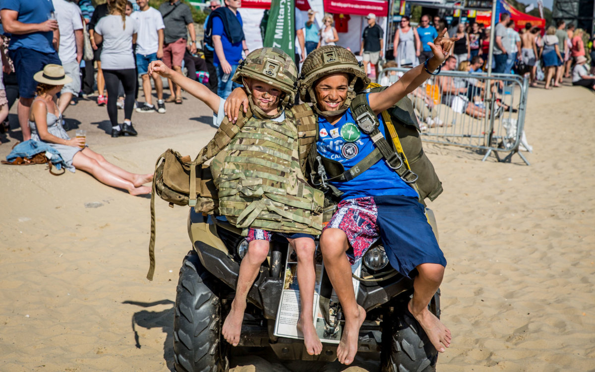 Kids dressed up in army gear sitting on a quad bike at the beach