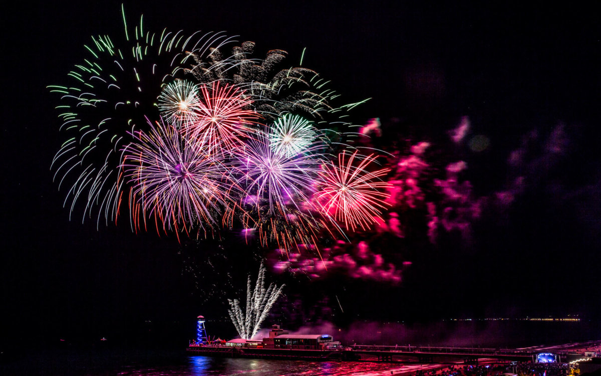 Red, purple and blue fireworks lighting up the night sky over Bournemouth pier