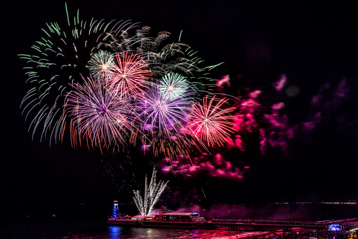 Multi colored fireworks exploding in the night sky above Bournemouth pier