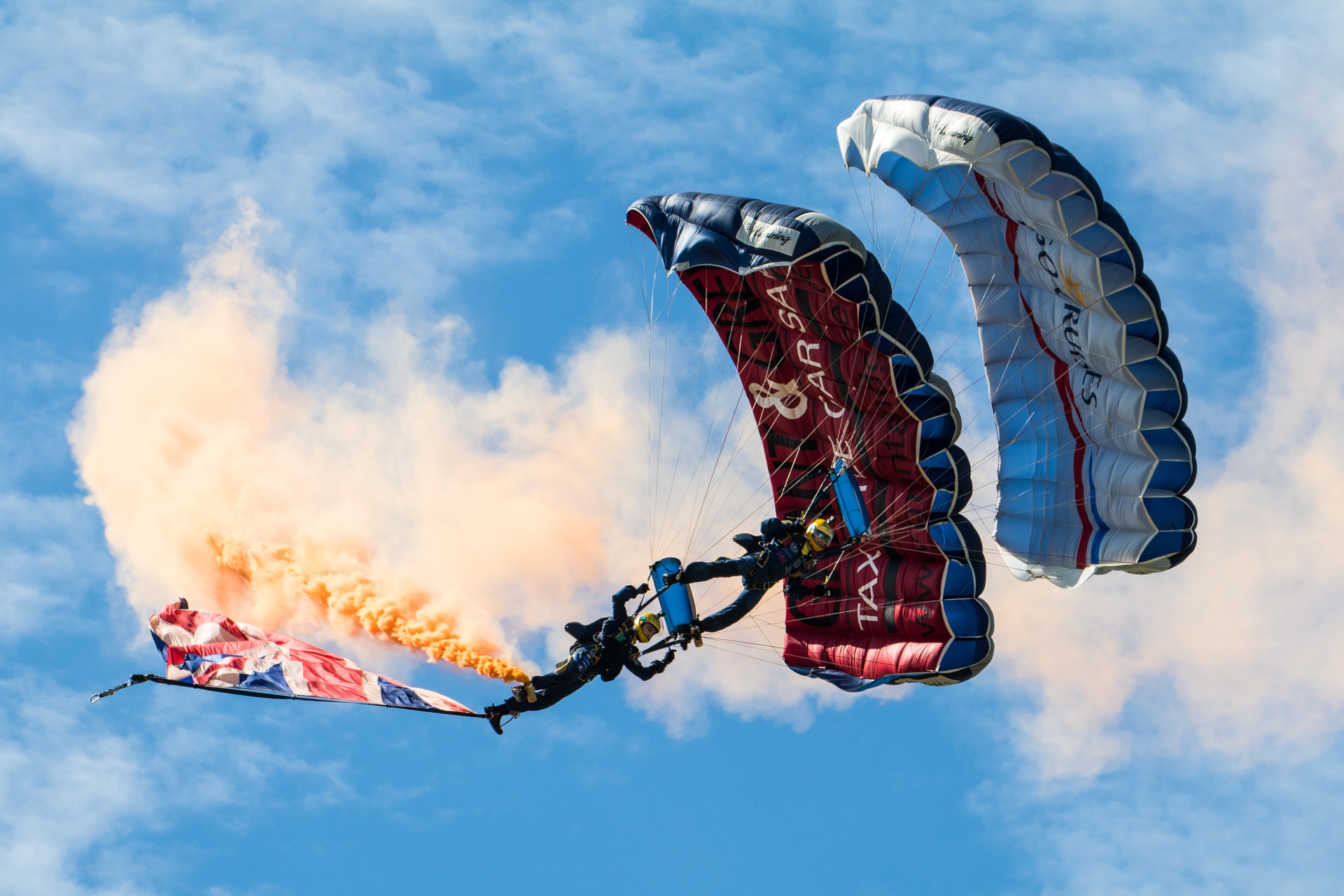 Two soldiers parachuting with flags and smoke coming off them during their Air festival show