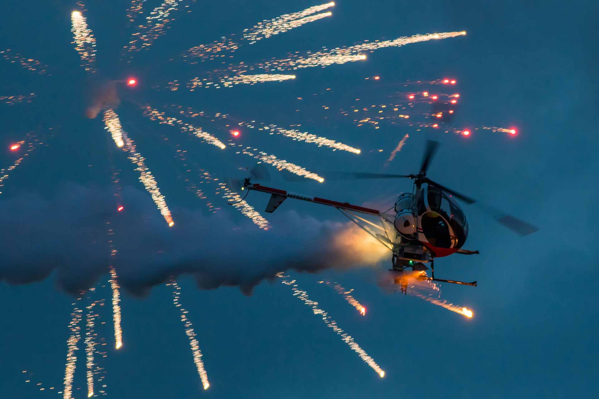Epic helicopter show firing off flares and performing maneuvers during the night show