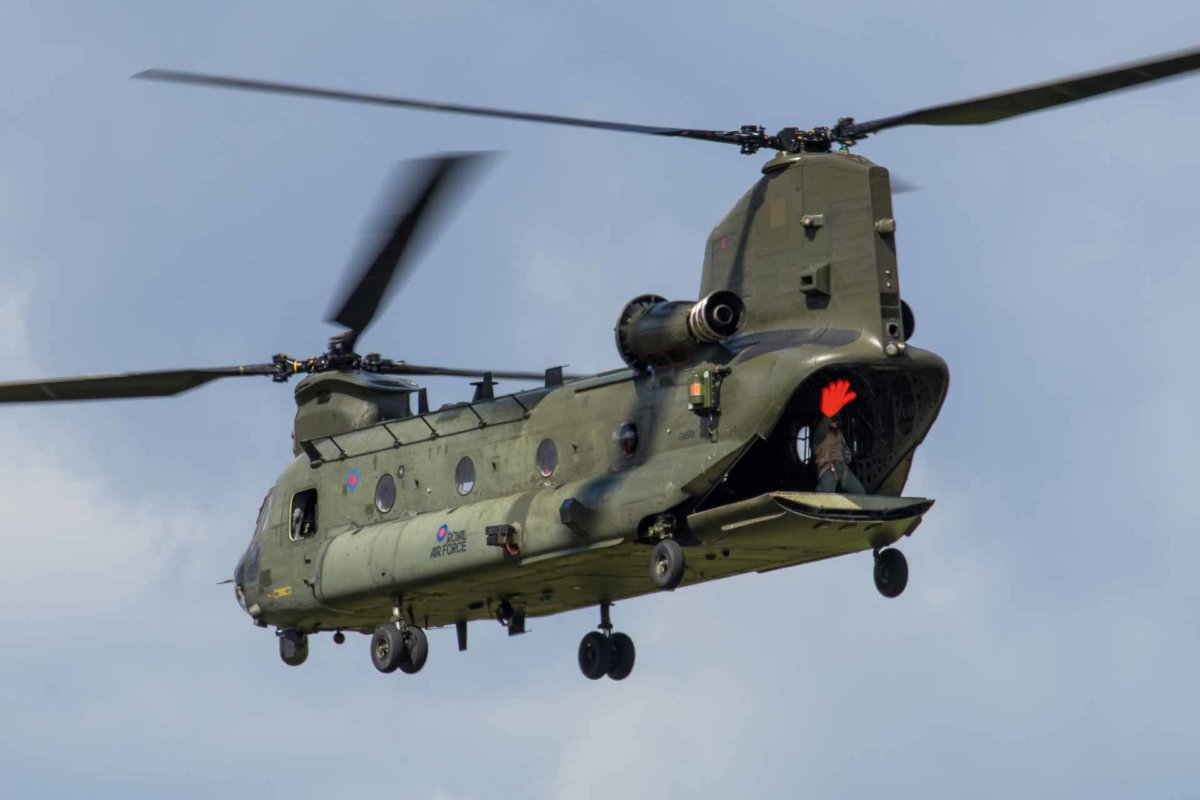 man waving a massive orange hand from the back of the chinook