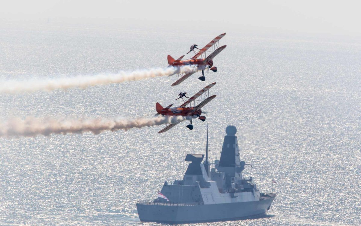 Two orange planes with people walking on the wings as they fly over a Royal Navy Ship