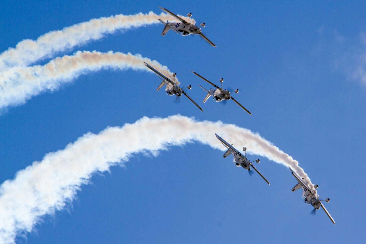 5 planes flying upside during their air performance for the festival