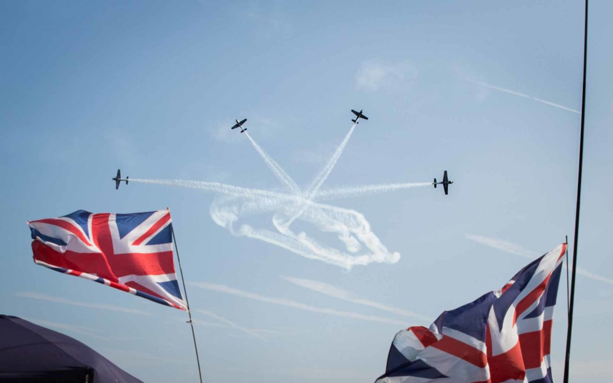 4 planes breaking formation during their show with two union jack flags