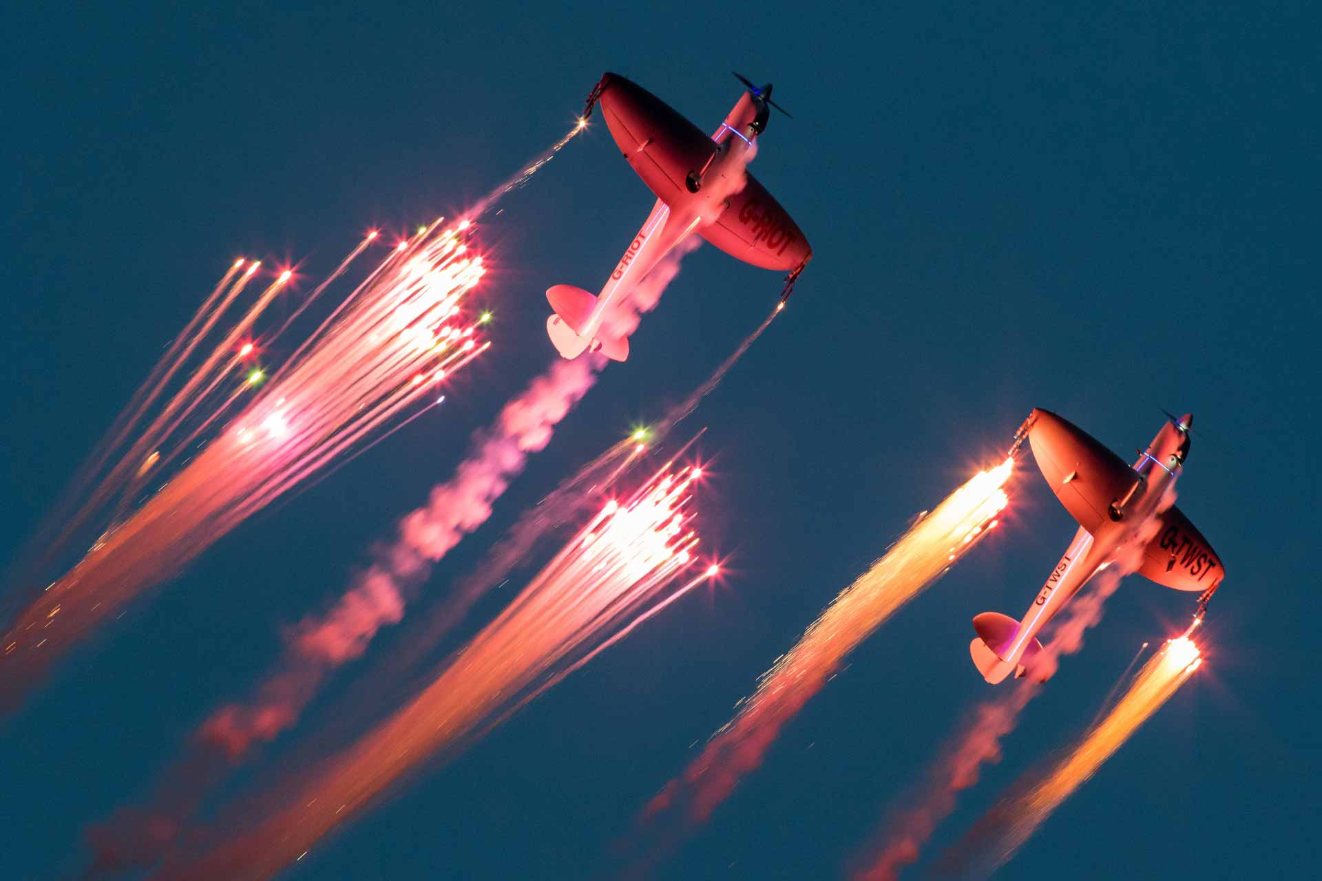 Two planes firing off colourful flares while they fly during the night show