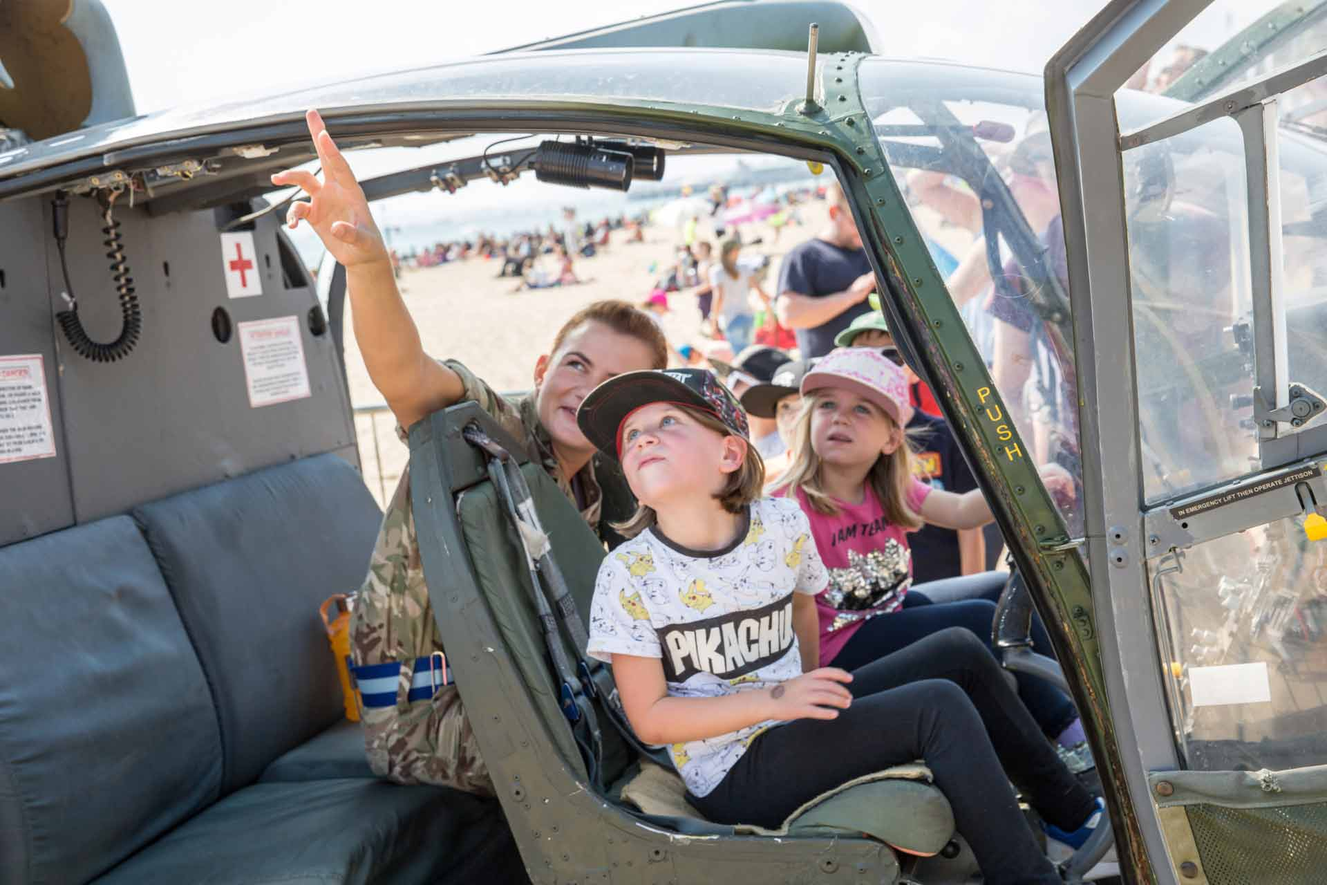Two young girls being shown around a helicopter by a solider