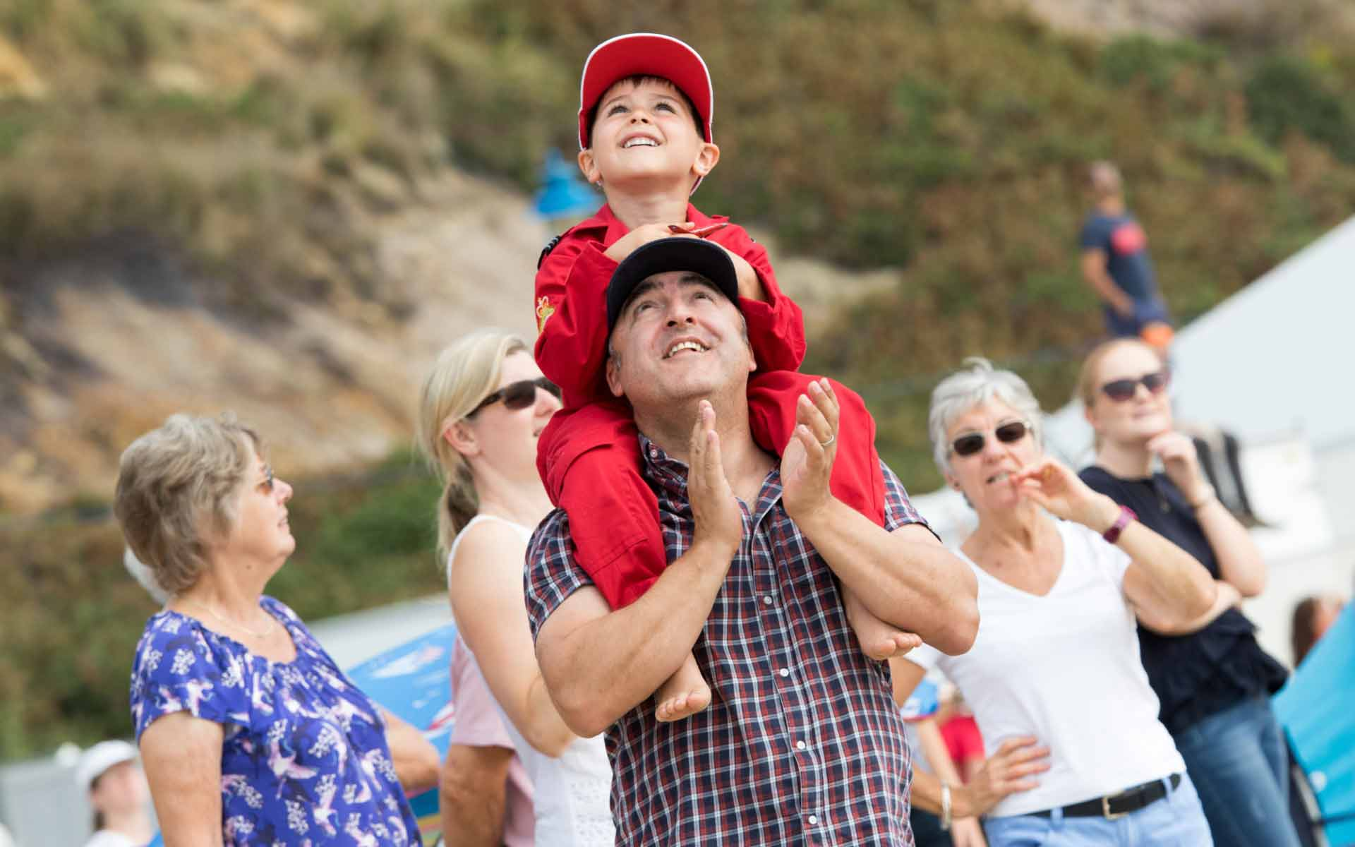 Kid sat on parents shoulders watching the planes performing in the sky