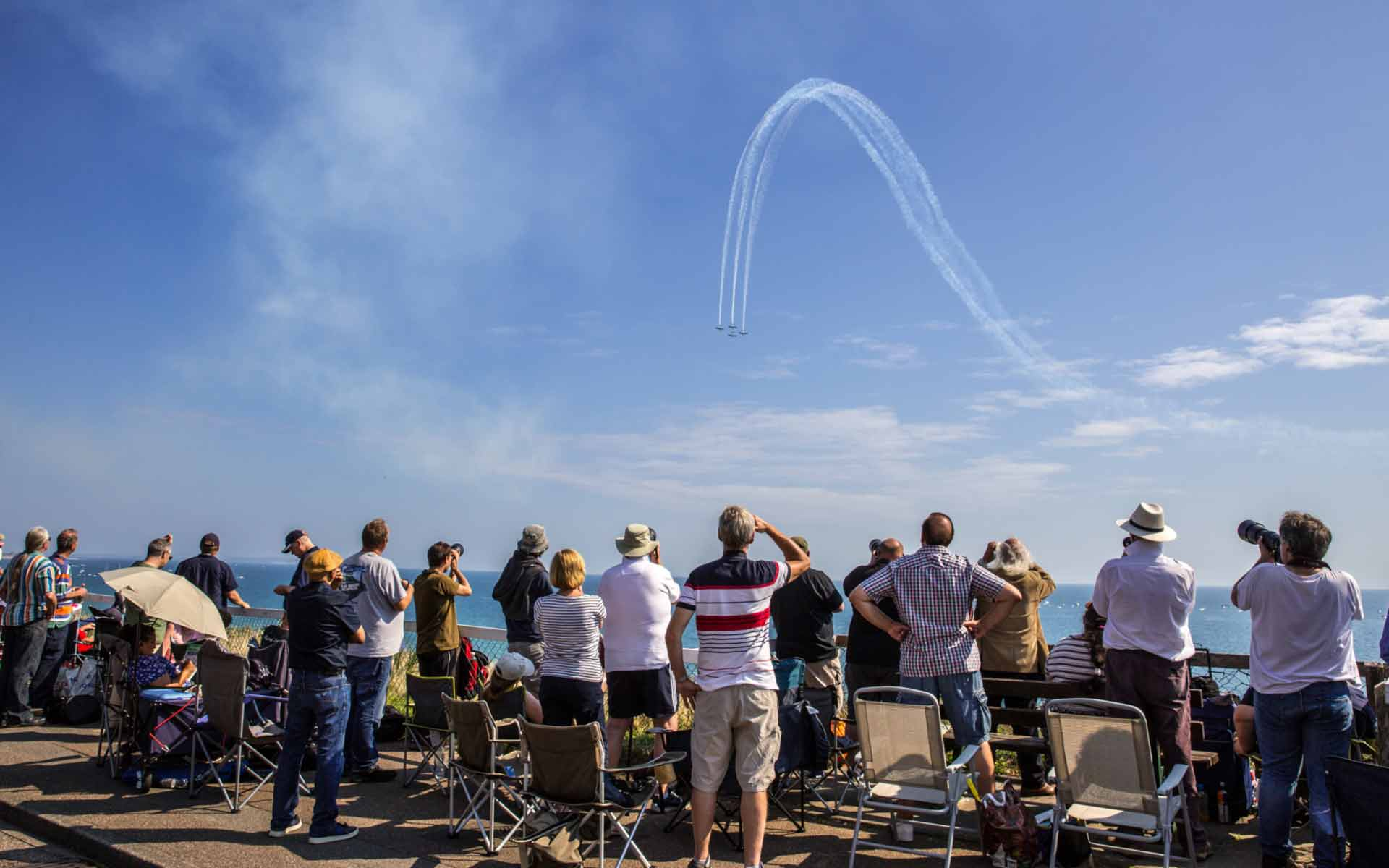 Planes performing whilst people watch and snap photos form the overcliff