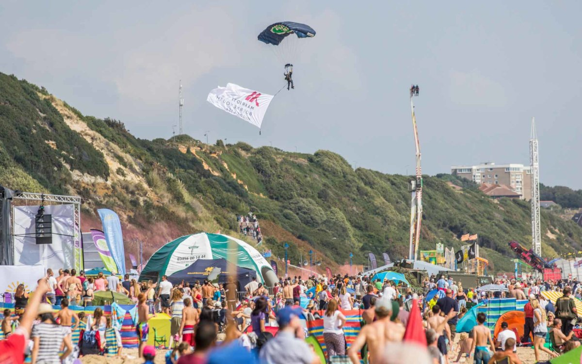 Parachutists preparing to land with a flag attached to him whilst people watch from the beach