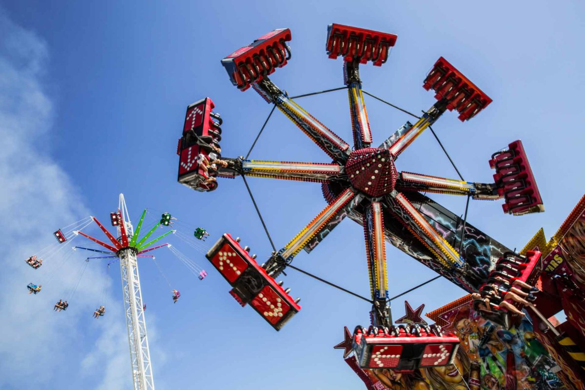 Two rides spinning festival visitors through the summer blue skies.