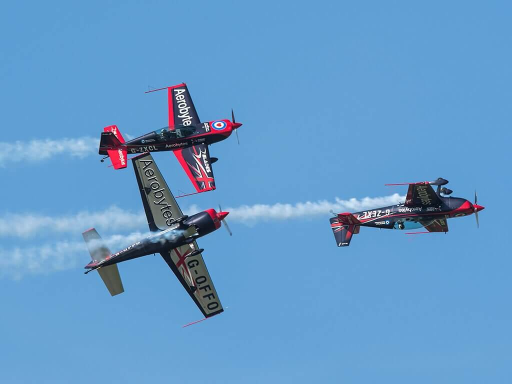 3 Blade aircraft's performing an Aerobatic manoeuvre during their flight show on a clear day