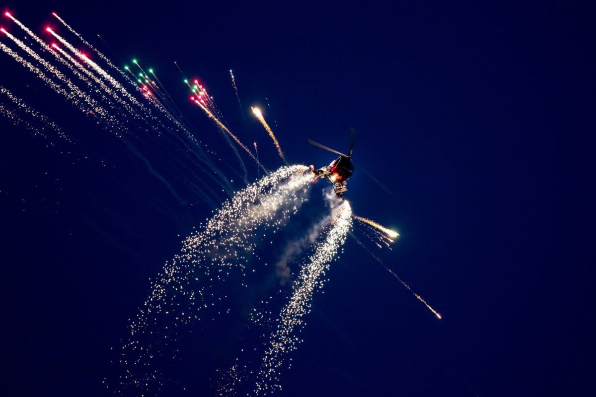 Crazy stuntman flying his helicopter during the night air show with fireworks flying off