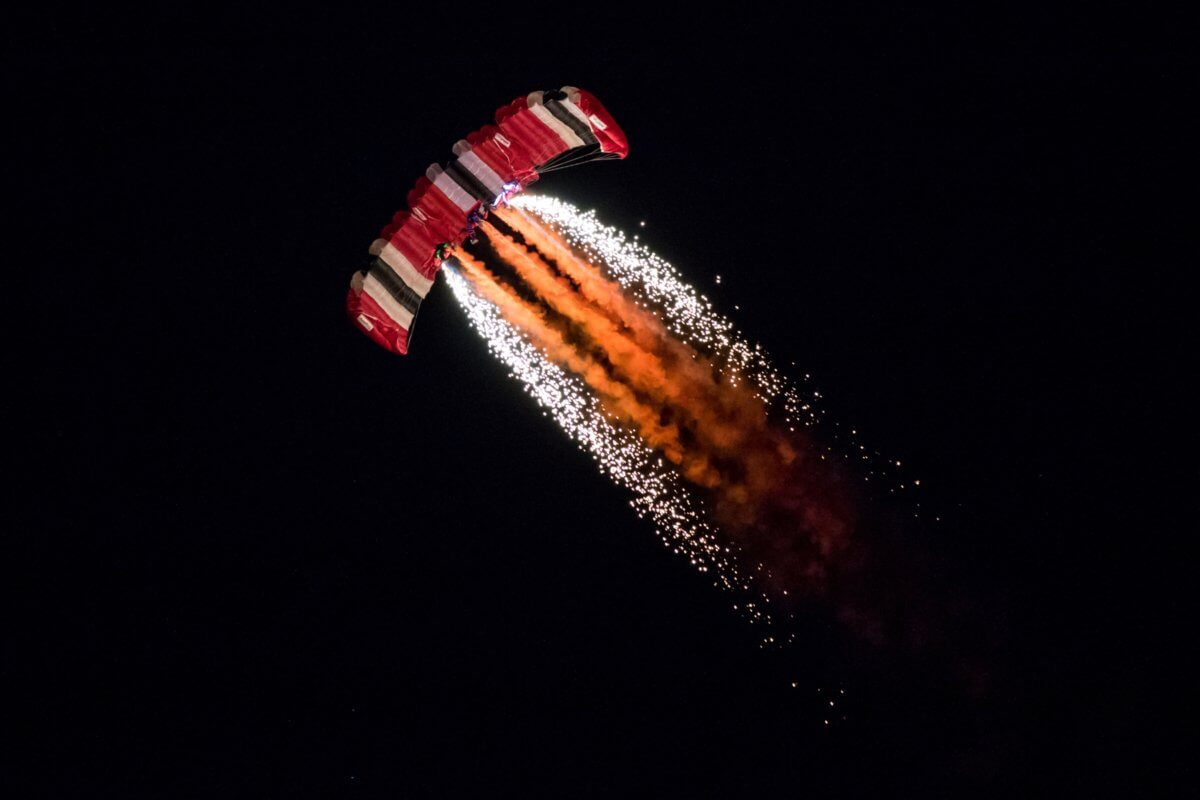 Immense scenes of two parachutists coming in to land with fireworks coming off them