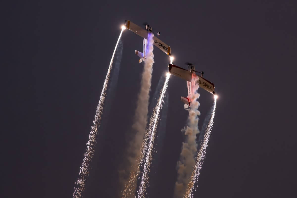 Two firefly planes illuminating the night sky with pyrotechnics during their air show performance