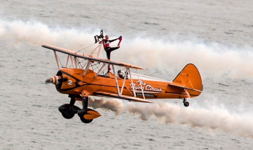 Death defying wing walkers performing on an Orange plane over Bournemouth's seaside