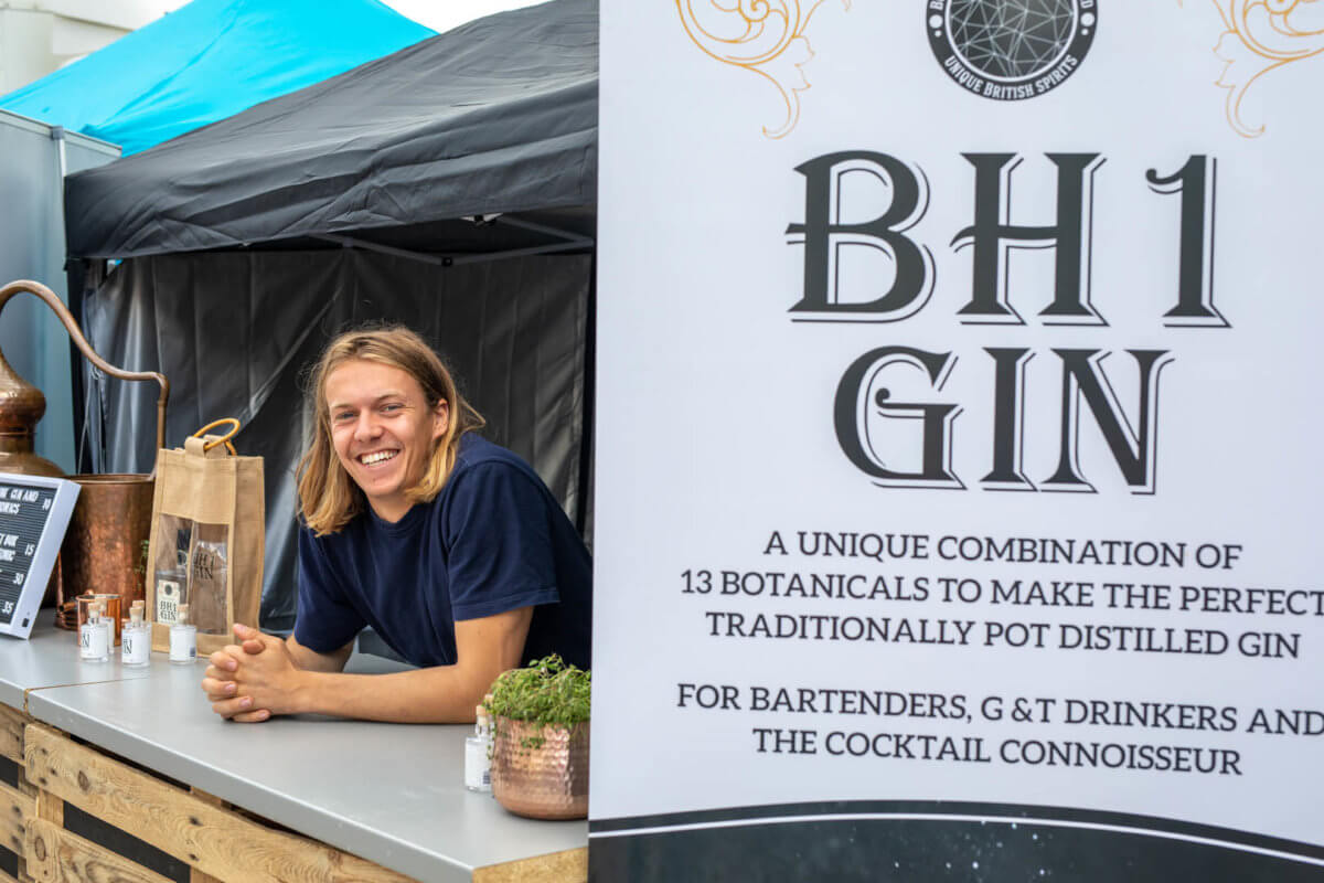 BH1 Gin trader smiling for the camera at his stall on the promenade