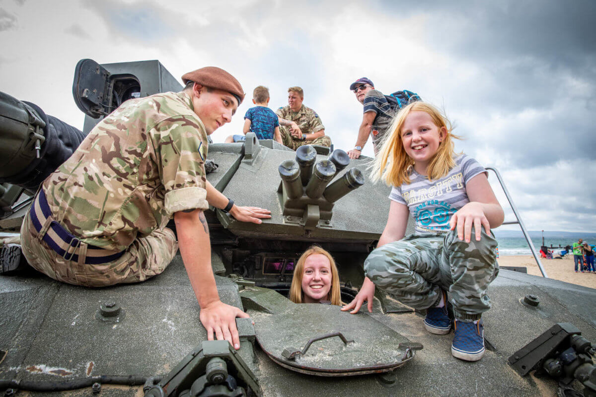 Two girls exploring the tank with a British soldier at the Bournemouth Air festival