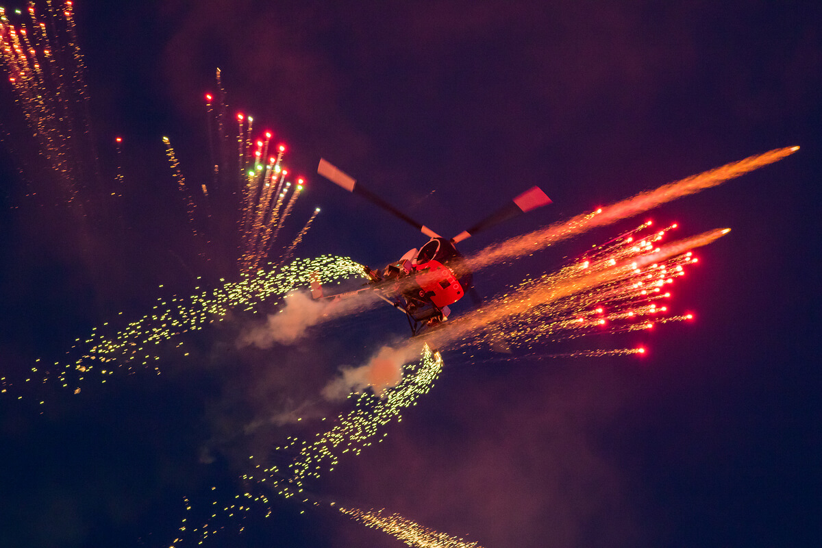 Otto piloting his Helicopter at night with fireworks flying off his craft