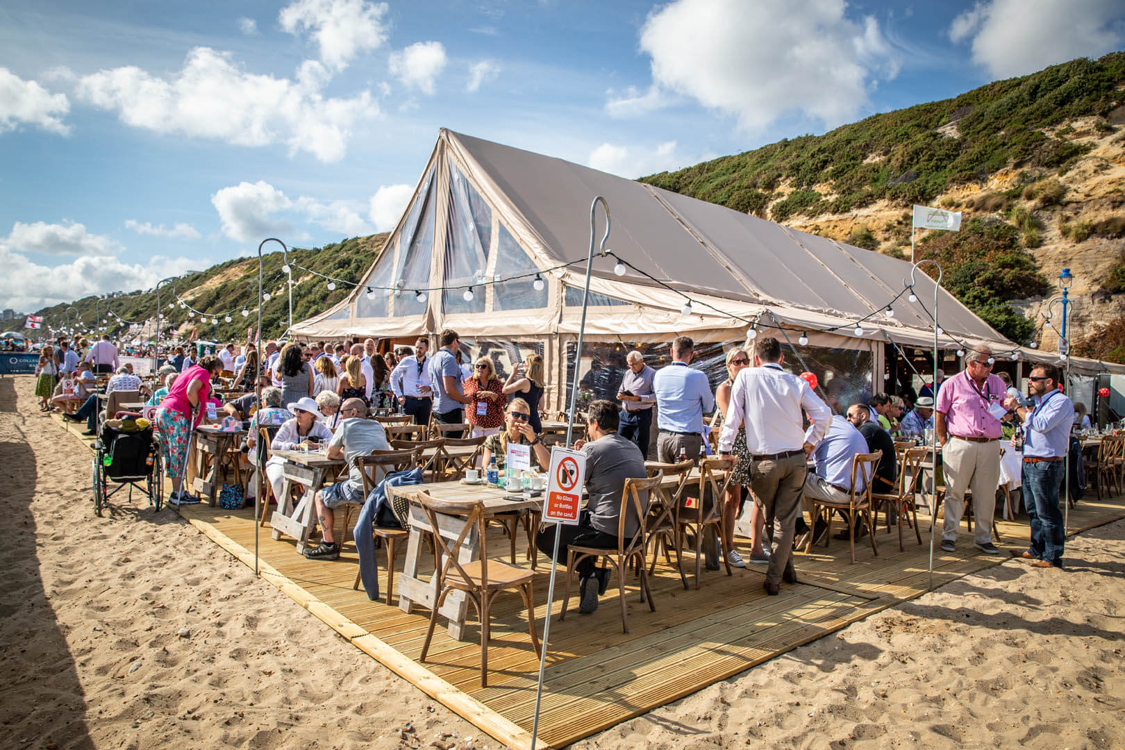 Crowds of people enjoying the hospitality tent on Bournemouth beach for the festival
