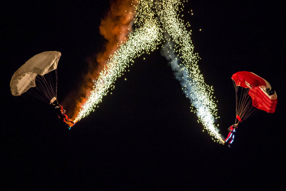 Two parachutists dropping in the night sky with pyrotechnics coming of them