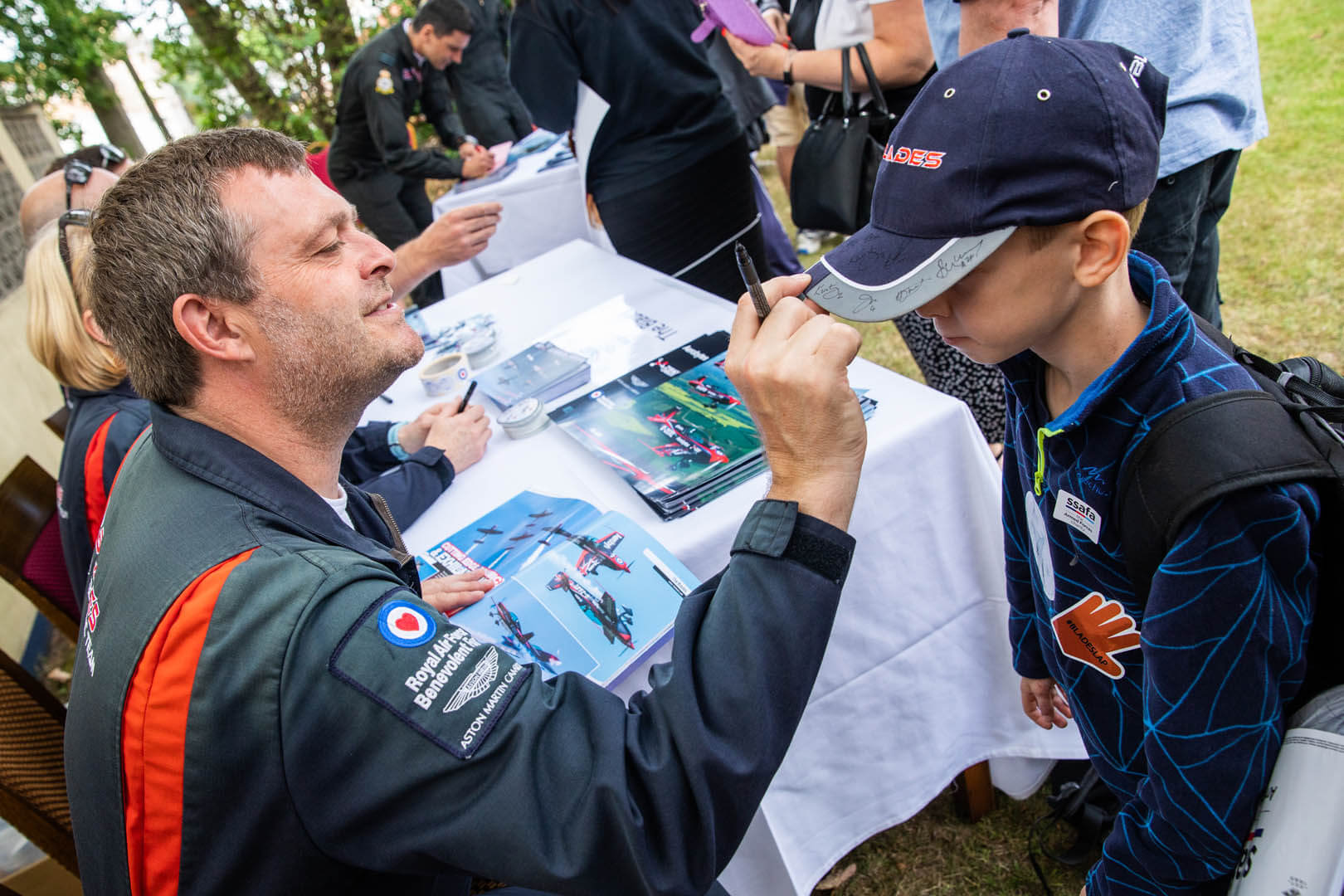 Blade pilot signing a fans hat at the Pilot meet and greet event in Bournemouth