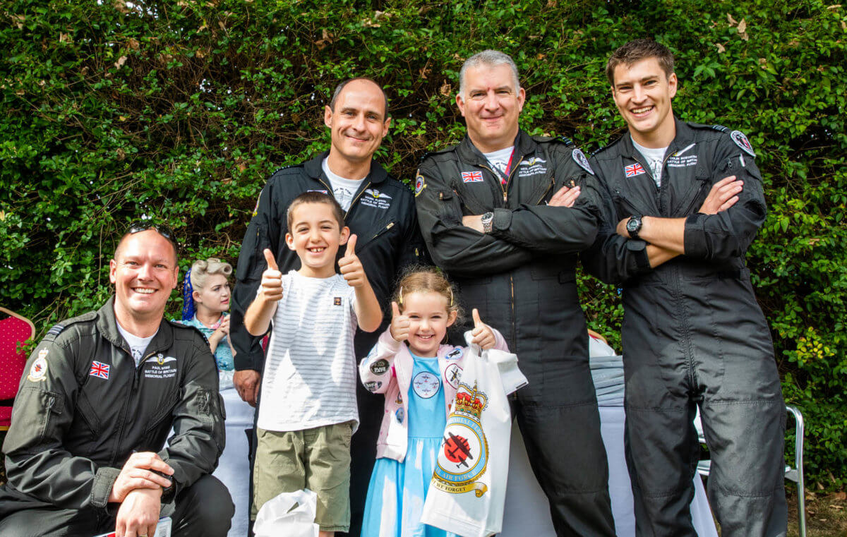 Pilots posing with two kids as they meet the world war display team
