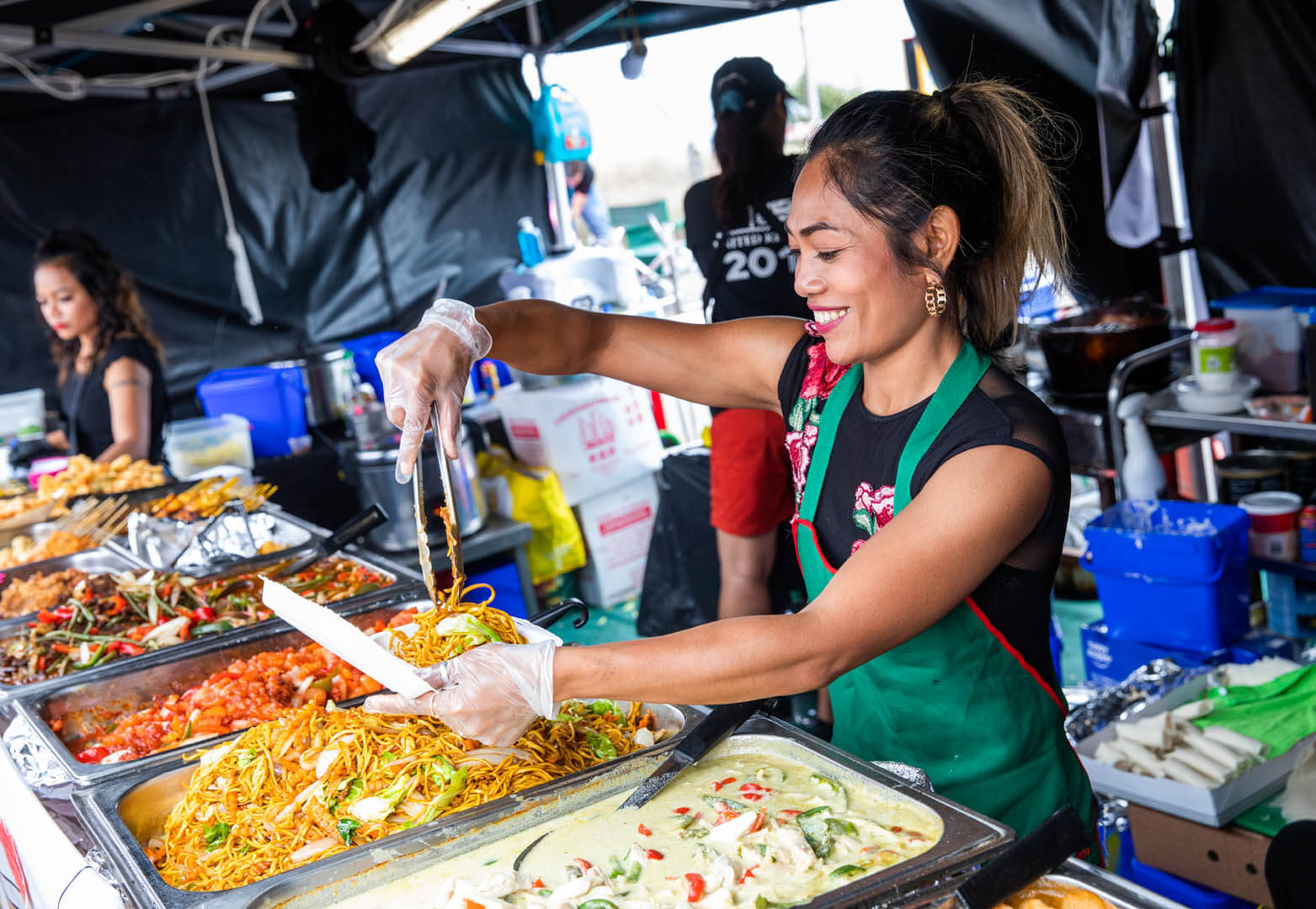 Trader dishing up and showing off her delicious array of Asian food at her stand