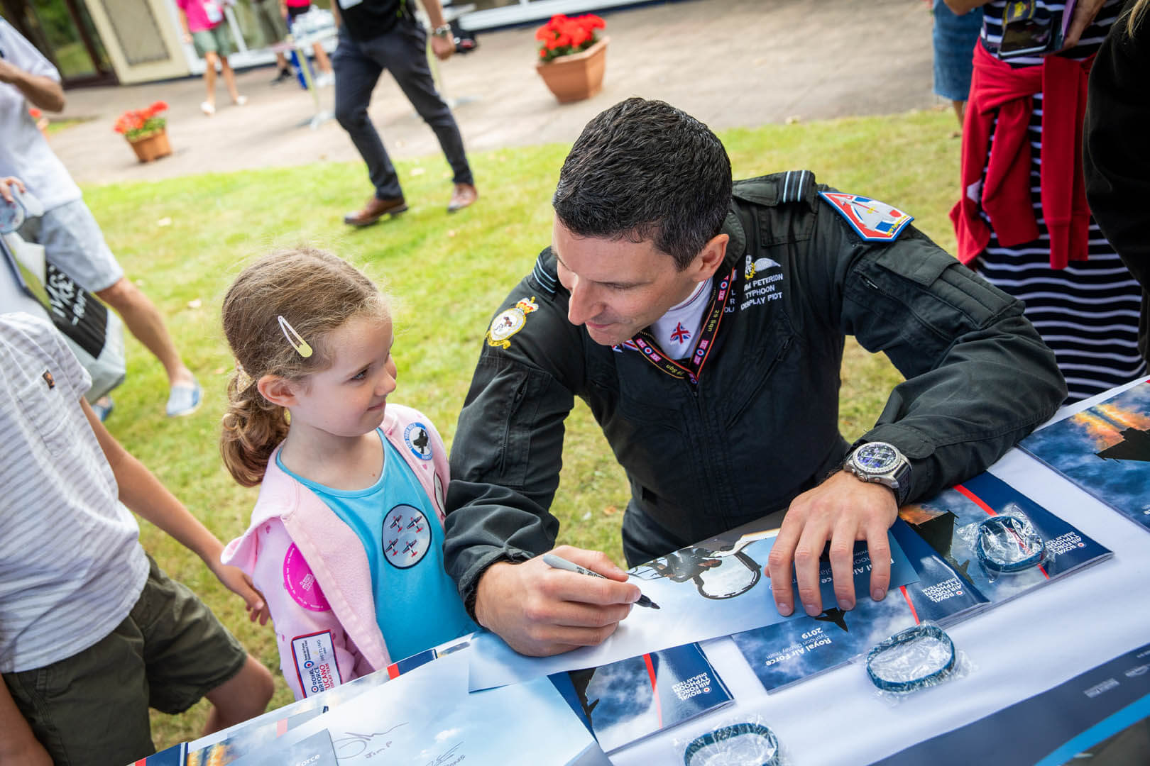 The Typhoon pilot signing a poster for a young child at the meet and greet