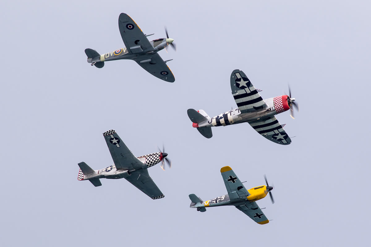 4 warbird planes flying in formation during their air show performance