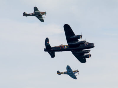 World war 2 memorial planes flying side by side as they entertain fans on the beach